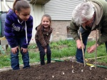 Mike shows some young gardeners how to plant onions